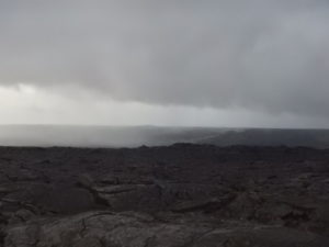 Do you see the steam rising from the lava flow as it travels down the mountain in the distance?